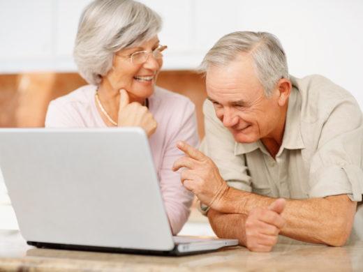 Senior man and woman using a computer laptop